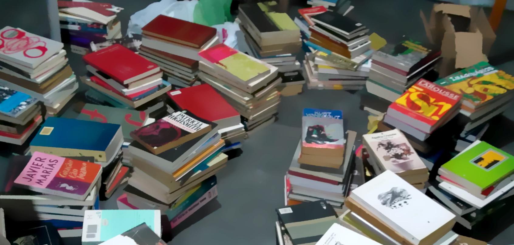 foto: livros empilhados e espalhados pelo chão