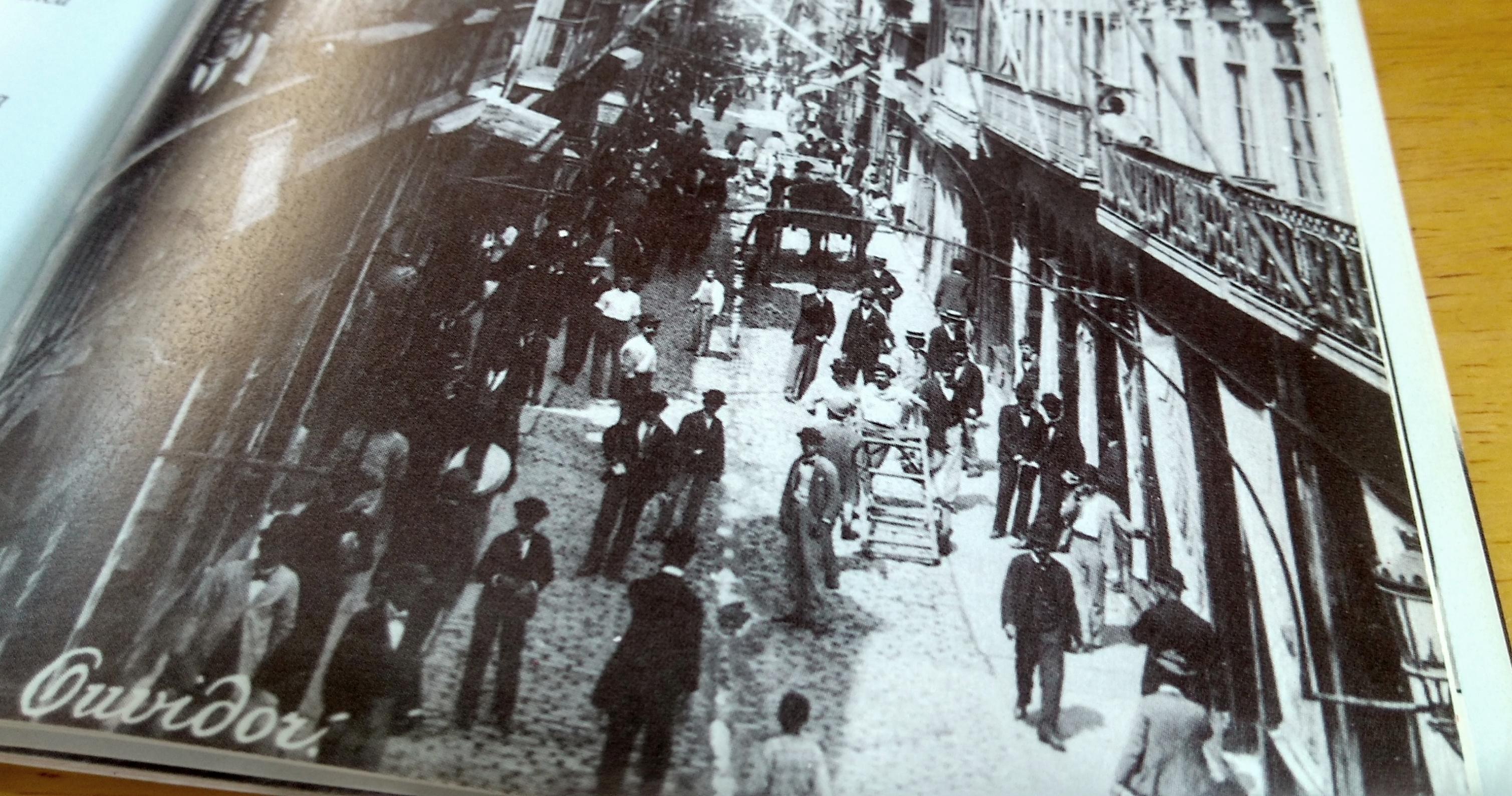 página de livro com foto antiga, em preto e branco, da rua do ouvidor, cheia de gente.