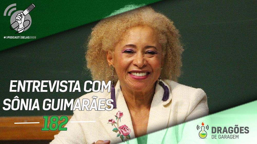 Foto da Prof. Sônia sorrindo. Ela tem olhos pequenos e o cabelo curto e armado, típico afro, mas pintado de um loiro fechado. Ela tá usando brincos longos e um terno branco, com 3 rosas bordadas na lapela direita